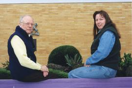 A man and a woman sitting on a ledge posing for a photo