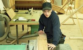 Male First Nations student wearing safety goggles and maneuvering a piece of wood [2 of 5 photogr...