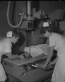 Medical radiography, 1968; two women positioning a man on his stomach under an x-ray generator fo...