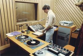 Broadcast Communication, 1970s; man standing at the work desk in a radio control room