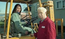 BCIT women in trades; forklift training, instructor beside a student driving a forklift [4 of 8 p...