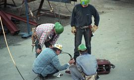 Ironwork, students wearing tool belts, hard hats and uniforms while using the tip a crane (?) [1 ...