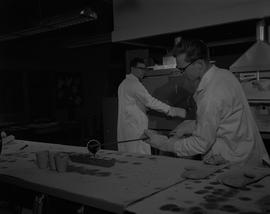 Mining, 1966; a man in a lab coat pouring black liquid into a mold ; man in a lab coat working in...
