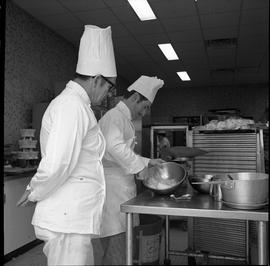BC Vocational School Cook Training Course ; student whipping ingredients in a bowl as instructor ...