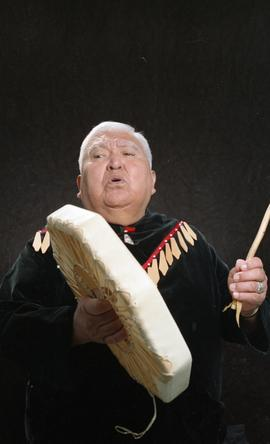 Bob George, First Nations elder, in First Nations garment playing an instrument [7 of 36 photogra...