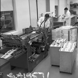 BCVS Graphic arts ; a man using a paper folding machine ; stacks of paper  and another man in bac...