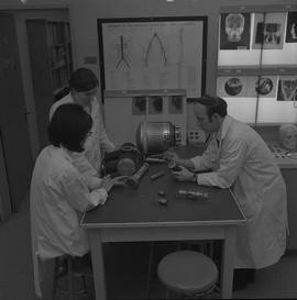 Medical radiography, 1968; three people in lab coats studying parts of an x-ray generator ; x-ray...