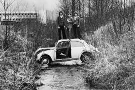1970's photograph of Guichon Creek with a Volkswagen VW Bug stuck in the creek, students standing...