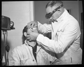 Industrial First Aid, Nanaimo; First Aid Attendant checking the eye of an industrial worker