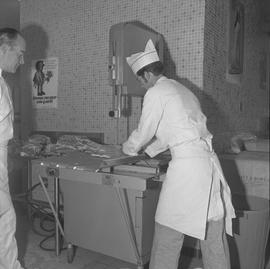 Meat cutting, 1968;  student holding a piece of meat and instructor watching