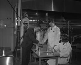 Food Processing Technology, 1966; instructor showing two students in lab coats a food processing ...