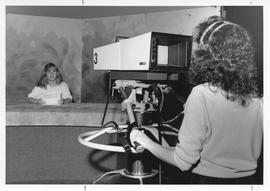 Broadcast Communications; woman sitting at a television news desk and another woman filming using...