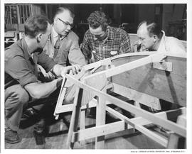 Four men looking at the front of a boat frame; Photo by the Division of Visual Education, Dept. o...