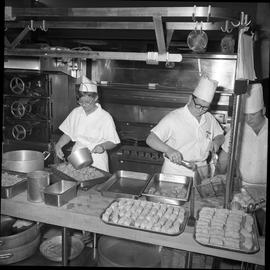 BC Vocational School Cook Training Course ; two students filling trays of food for the cafeteria ...