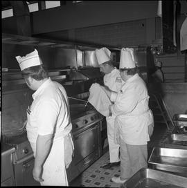 BC Vocational School Cook Training Course ; a student frying meat on a grill ; student and instru...