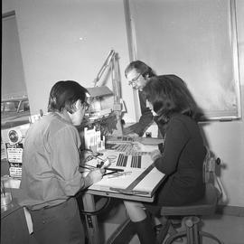 BCVS Graphic arts ; three people at a desk looking at illustrations [3 of 11]