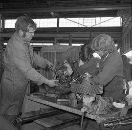 BCVS Heavy duty mechanic program ; an instructor and two students working on a disassembled motor