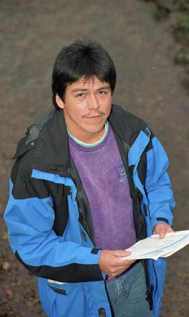 Male First Nations BCIT graduate standing outside holding a notebook [14 of 16 photographs]