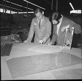BCVS Glazier program ; two men looking at blueprints ; a large piece of glass on the table