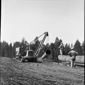 Heavy duty equipment operator, Nanaimo ; a pipelayer moving a large pipe ; two men watching