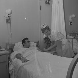 Nursing, 1968; a nurse attending to a patient checking temperature
