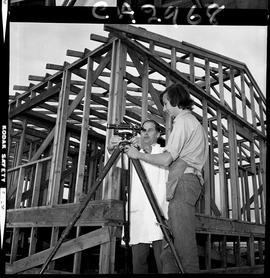 B.C. Vocational School; Carpentry Trades student watching as an instructor adjusts construction e...