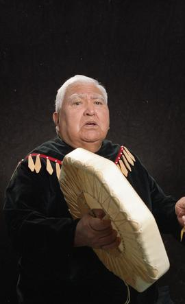 Bob George, First Nations elder, in First Nations garment playing an instrument [6 of 36 photogra...