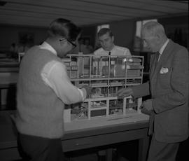 Forest Products, 1964; three men looking at a small scale model of a factory