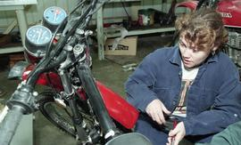 BCIT women in trades; power equipment, students in uniforms using automobile tools on motor parts...