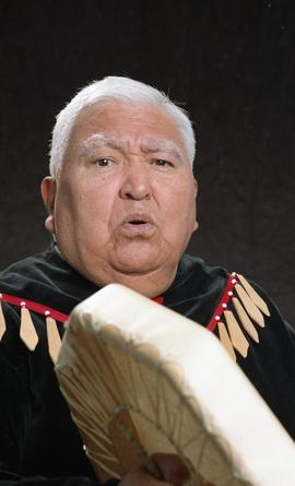 Bob George, First Nations elder, in First Nations garment playing an instrument [3 of 36 photogra...