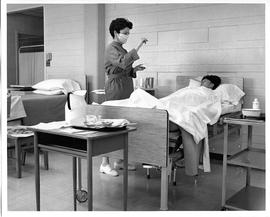 BCVS Nursing student, wearing mask, looking at something in her hand; near patient in bed (ca. 1968)