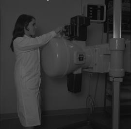 Medical radiography, 1968; woman in a lab coat putting film(?) in radiography equipment [2 of 2]