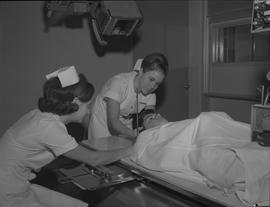 Medical radiography, 1968; two women positioning a man on his back under an x-ray generator for a...