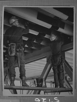 Structural steel; two men working on structural beams under A. Murray Mackay bridge connecting Ha...
