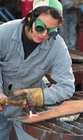 BCIT women in trades; welding, students wearing safety gear while using a small torch inside a we...