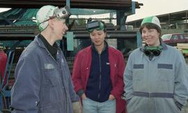 BCIT women in trades; welding, students talking while standing around inside a welding shop [1 of...