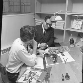BCVS Graphic arts ; two men sitting at a desk looking at illustrations and lettering [1 of 2]