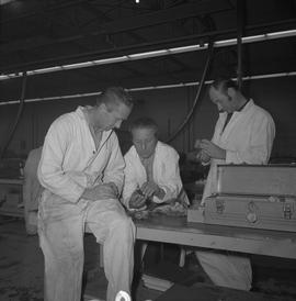 Small engine repair, 1971, Prince George; three men looking at pieces of an engine