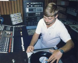 Broadcast Communications; man using a record player in a radio control booth