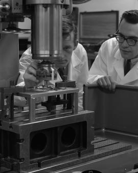 Mechanical technology, 1967; two men in lab coats using a machine to drill into metal [2 of 2]
