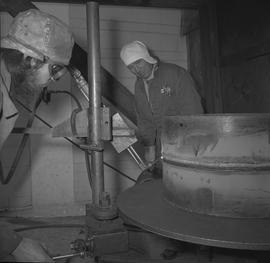 Welding, Prince George, 1968; instructor wearing his hat sideways and watching a man wearing prot...