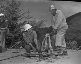Logging, 1967; a man holdings a large metal cable and another man using logging equipment