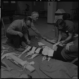 Industrial First Aid, Nanaimo; two men putting a leg splint on someone ; man bandaging the other leg