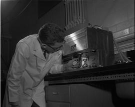 Gas and Oil, 1966; man in a lab coat holding a stop watch and using Labline testing equipment
