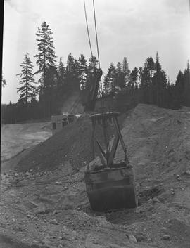 Heavy duty equipment operator, Nanaimo ; bucket of an excavator ; excavator and forest in background