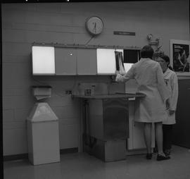 Medical radiography, 1968; two women in lab coats talking, one of the women is hanging a x-ray on...