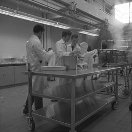 BCIT Food Technology program ; two students measuring the weight of food ; students in background