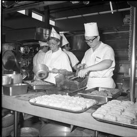 BC Vocational School Cook Training Course ; two students filling trays of food for the cafeteria