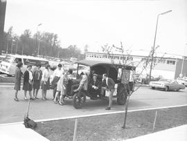 Students standing around a car from the 1920s(?) on campus