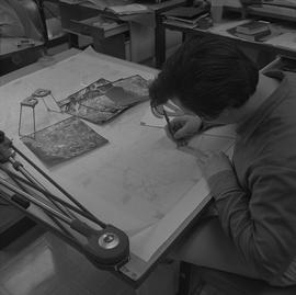 Map drafting, Victoria, 1968; man drafting a map ; aerial photographs and stereoscope on desk